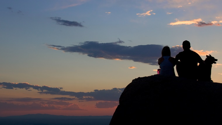 A couple sit with their dog on a rock looking at the sunset over the mountains in the distance.