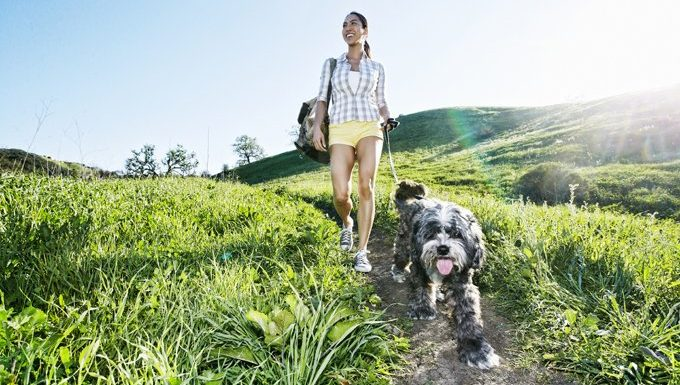 woman walks dog in nature