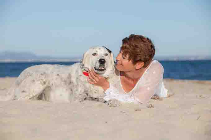 Woman and her dog lay in the sand at the beach cuddling.