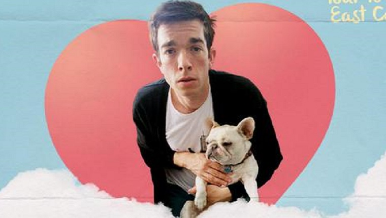 John Mulaney holds his white French Bulldog in front of a heart-shaped graphic.