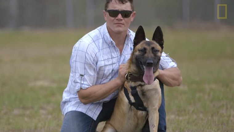 Staff Sgt. Julian McDonald is in civilian clothes kneeling next to Layka the German Shepherd in a field.