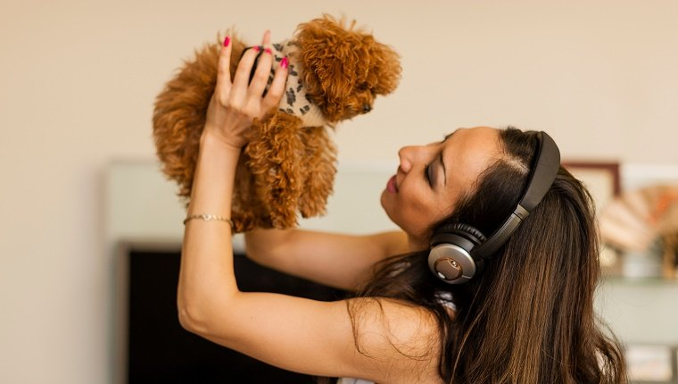 Mid adult woman wearing headphones and dancing with dog