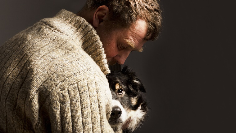 man embracing dog