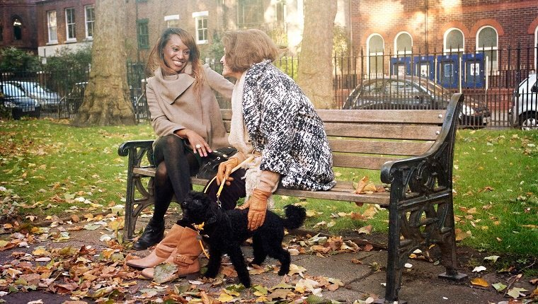 A natural view of two women, dressed in warm clothing, as they chat together on an iron bench in an Autumnal London park. One of the women is a mature lady who is gently holding on to a small black poodle.