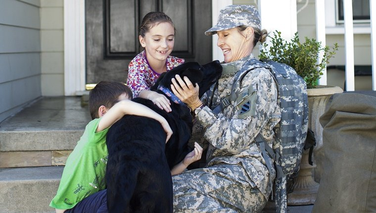 Military Mom greeting kids and dog on front porch.