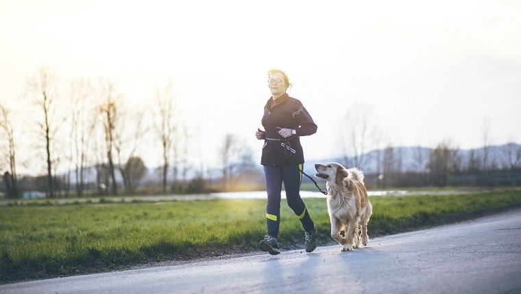 A senior woman running outdoors with her dog
