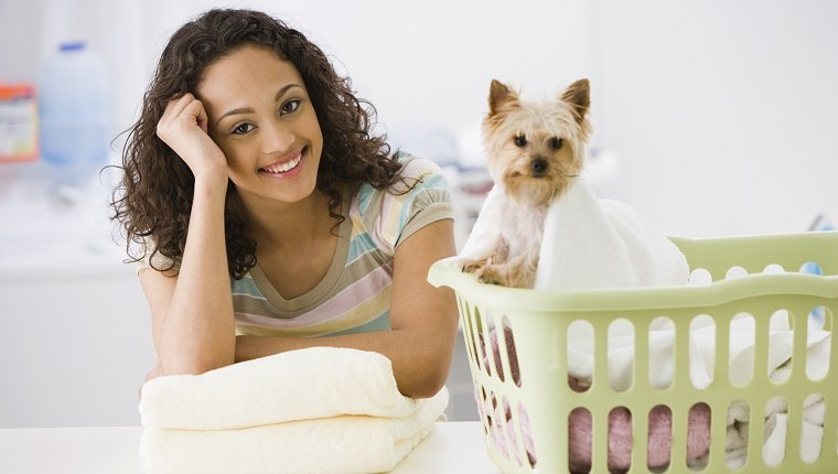Mixed race teenage girl in laundry room with dog