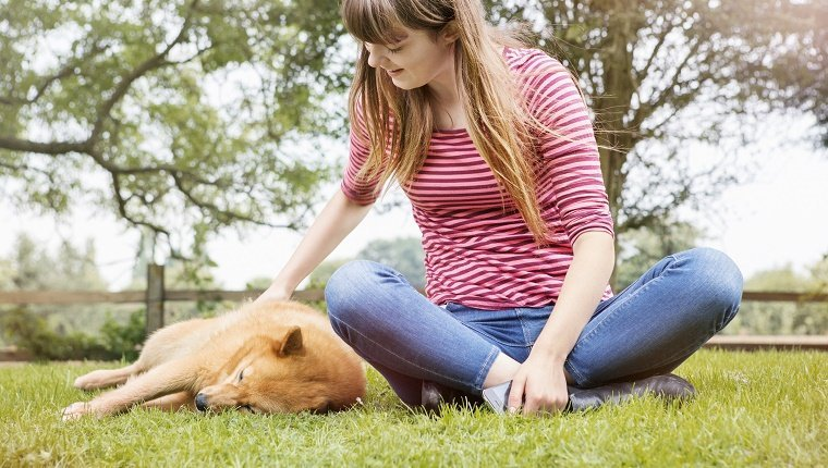 yung woman strokes dog snoozing in grass.