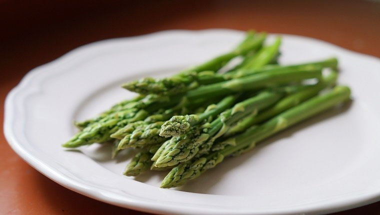 Healthy summer vegetable: Green aspargus on white plate.