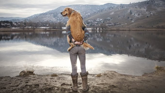 man holds dog near lake and mountains