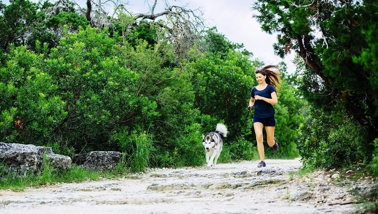 Caucasian woman jogging with dog