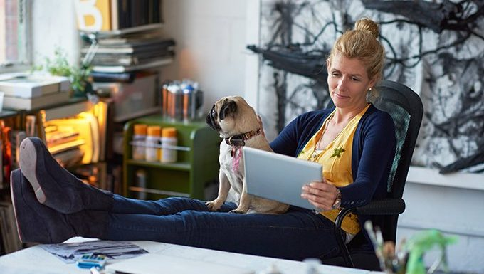 dog sits with woman looking at tablet