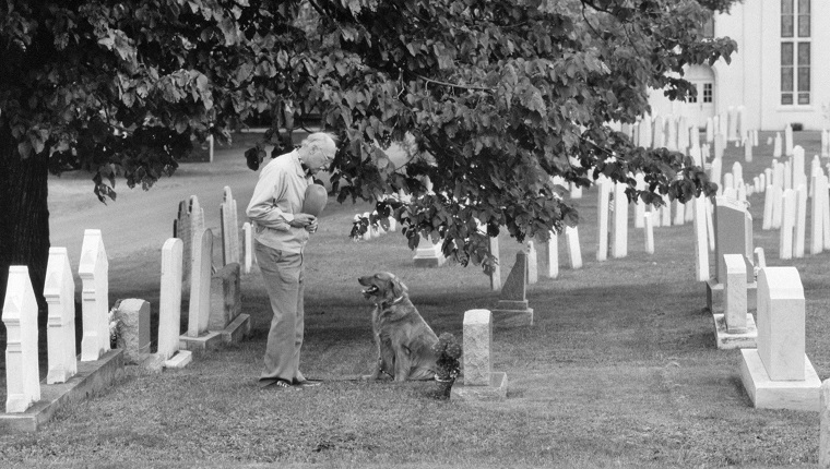 ELDERLY MAN HAT OVER HIS HEART AND PET DOG VISITING GRAVE OF LOVED ONE IN CHURCHYARD CEMETERY (Photo by Camerique/ClassicStock/Getty Images)