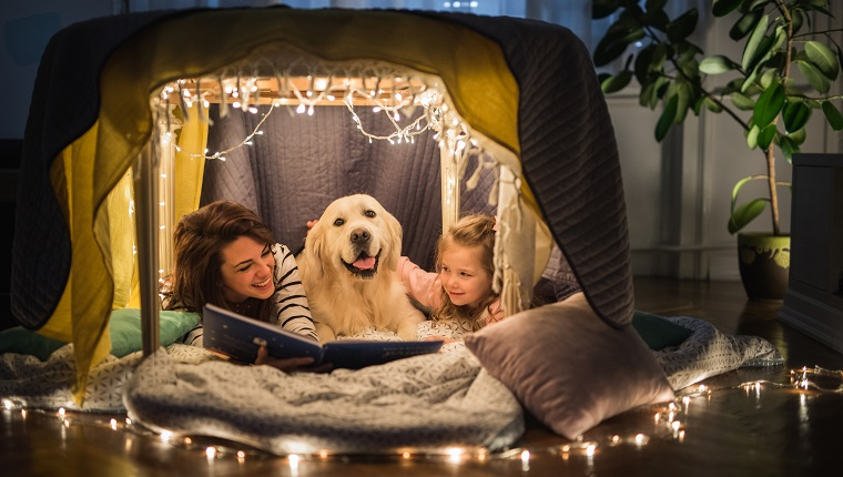Young happy mother reading a book to her small girl while being in a tent at home with their dog.