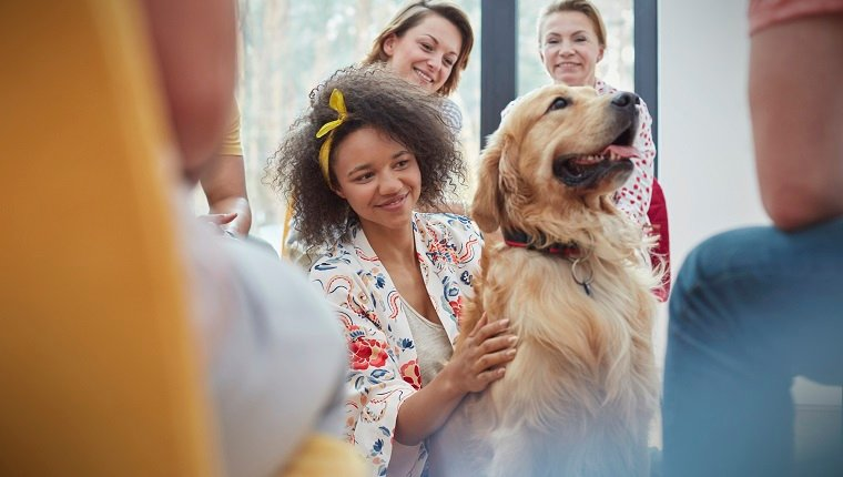 Woman petting dog in group therapy session
