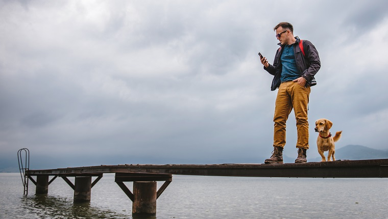 Man standing on wooden dock on stormy weather with his dog and using smart phone. He is wearing red backpack, blue jacket and leather boots