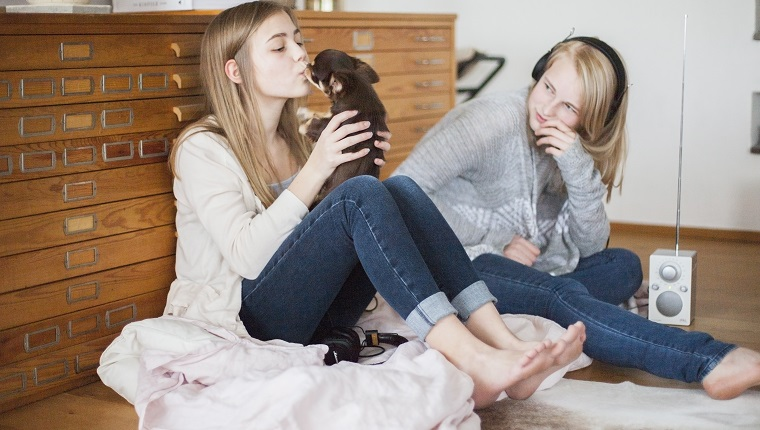 Sisters in room with radio and dog