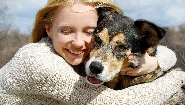 a loving and candid portrait of a happy woman hugging her large German Shepherd dog.